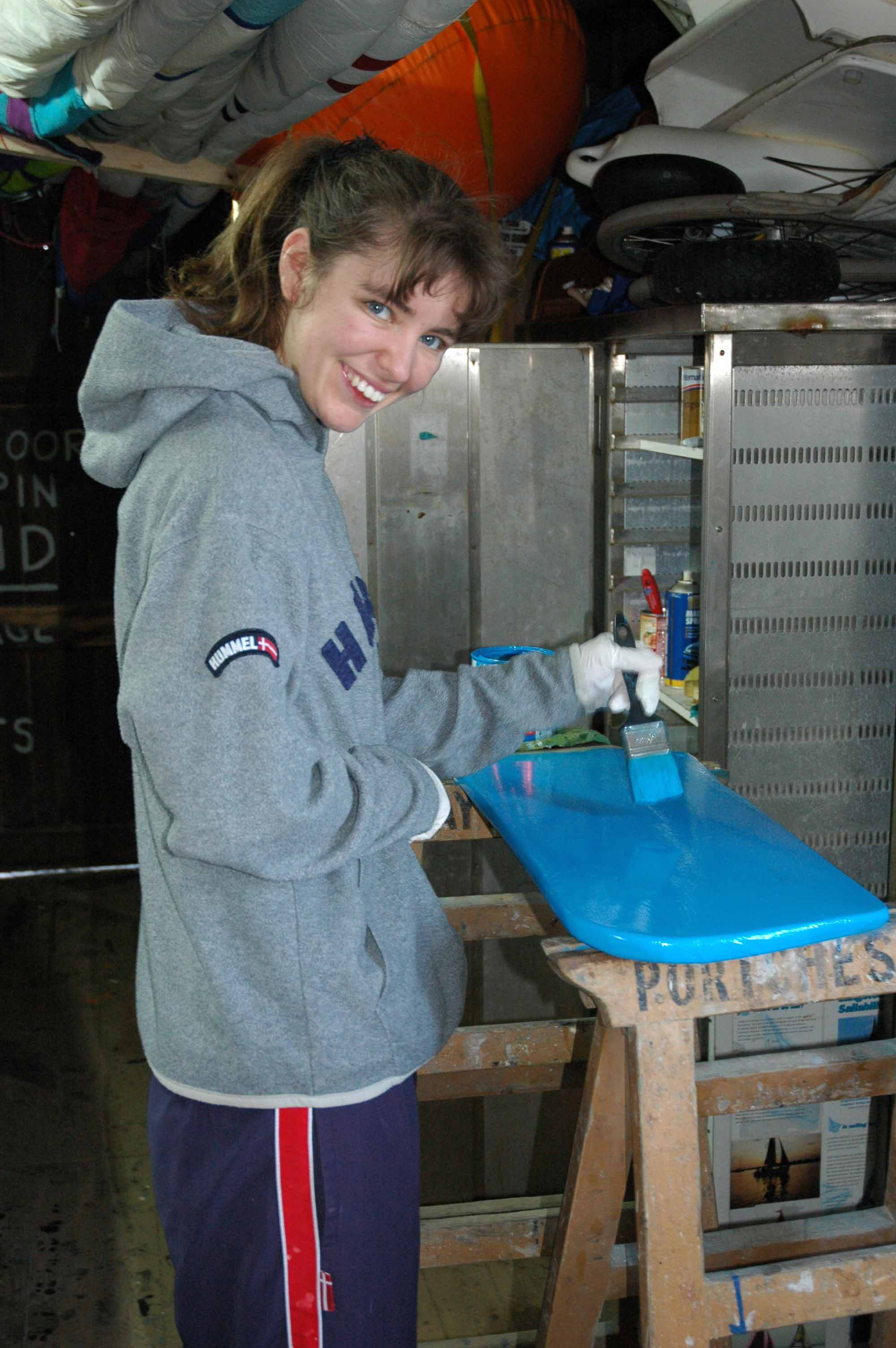 Gina painting a rudder.